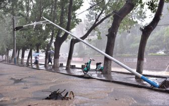 DENGFENG, CHINA - JULY 20: People walk by a fallen electric pole on July 20, 2021 in Dengfeng, Zhengzhou City, Henan Province of China. Torrential rains hit Henan since July 16, causing floods in many parts of the province on Monday and Tuesday. (Photo by VCG/VCG via Getty Images)