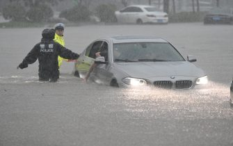 ZHENGZHOU, CHINA - JULY 20: Policemen evacuate traffic in floodwater near Zhengzhou Railway Station on July 20, 2021 in Zhengzhou, Henan Province of China. Torrential rains hit Henan since July 16, causing floods in many parts of the province on Monday and Tuesday. (Photo by Zhu Zhe/VCG via Getty Images)
