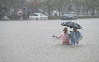 ZHENGZHOU, CHINA - JULY 20: People walk in floodwater near Zhengzhou Railway Station on July 20, 2021 in Zhengzhou, Henan Province of China. Torrential rains hit Henan since July 16, causing floods in many parts of the province on Monday and Tuesday. (Photo by Zhu Zhe/VCG via Getty Images)