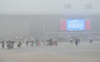 ZHENGZHOU, CHINA - JULY 20: Passengers walk in floodwater in front of Zhengzhou Railway Station on July 20, 2021 in Zhengzhou, Henan Province of China. Torrential rains hit Henan since July 16, causing floods in many parts of the province on Monday and Tuesday. (Photo by Zhu Zhe/VCG via Getty Images)
