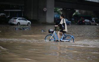 A woman pedals through a flooded street following heavy rains, in Zhengzhou in China's central Henan province on July 22, 2021. (Photo by Noel Celis / AFP) (Photo by NOEL CELIS/AFP via Getty Images)