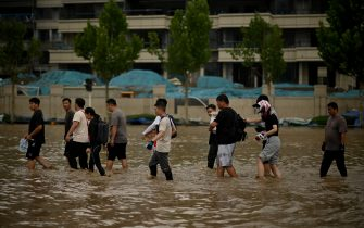 People wade through a flooded street following a heavy rain in Zhengzhou, in China's Henan province on July 22, 2021. (Photo by Noel Celis / AFP) (Photo by NOEL CELIS/AFP via Getty Images)
