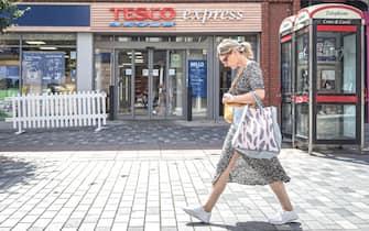 Donna davanti a un supermercato Tesco in Inghilterra