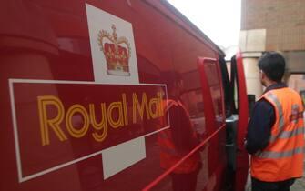 Un postino della Royal Mail davanti al furgone del servizio postale britannico