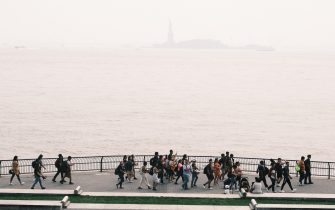 NEW YORK, NEW YORK - JULY 20: A group protesting the situation in Cuba walks by New York Harbor which sits under a cloud of haze on July 20, 2021 in New York City. According to data from the National Oceanic and Atmospheric Administration, wildfire smoke from the west has arrived in the tri-state area creating decreased visibility and a yellowish haze in many areas. (Photo by Spencer Platt/Getty Images)