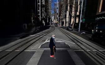 Una cittadina attraversa una strada a Sydney, durante il lockdown per l'emergenza Covid