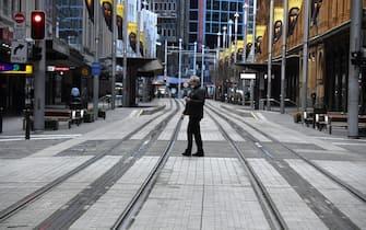 Un cittadino passeggia per le strade deserte di Sydney durante il lockdown
