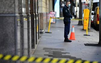 Un poliziotto sorveglia l'ingresso di un Covid hotel a Sydney
