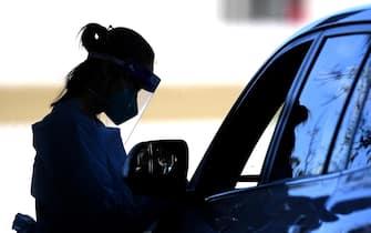 Un'operatrice sanitaria effettua un tampone per la rilevazione del coronavirus a Sydney