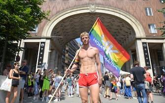Un giovane con la bandiera arcobaleno al Gay pride di Budapest