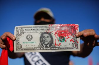 A man holding a dollar bill with the face of the Brazilian President Jair Bolsonaro and blood, takes part in a demonstration against Bolsonaro's handling of the COVID-19 pandemic in Brasilia, on July 3, 2021. - Thousands of Brazilians took to the streets Saturday to protest against President Jair Bolsonaro, who faces an investigation over an allegedly corrupt Covid vaccine deal. (Photo by Sergio LIMA / AFP) (Photo by SERGIO LIMA/AFP via Getty Images)