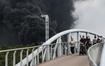 epa09369790 People walk over a pedestrian overcrossing as smoke billows in the background from the chemical industry area of 'Chempark' in Leverkusen, Germany, 27 July 2021. The city of Leverkusen has warned citizens on its official website, that an explosion with an unknown cause occurred on the day at the site of the Chempark. Residents are asked to stay indoors and to keep windows and doors closed.  EPA/SASCHA STEINBACH