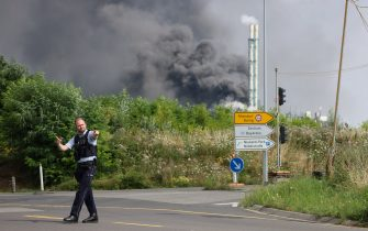 27 July 2021, North Rhine-Westphalia, Leverkusen: A policeman is standing near an access road to the Chempark over which a dark cloud of smoke is rising. After an explosion fire brigade, rescue forces and police are currently in large-scale operation, the police explained. Due to the damage, the busy A1 motorway near Leverkusen has been closed. Photo: Oliver Berg/dpa (Photo by Oliver Berg/picture alliance via Getty Images)