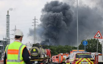 27 July 2021, North Rhine-Westphalia, Leverkusen: Emergency vehicles of the fire brigade stand not far from an access road to the Chempark over which a dark cloud of smoke is rising. After an explosion, fire brigade, rescue forces and police are currently in large-scale operation, the police explained. Due to the damage, the busy A1 motorway near Leverkusen has been closed. Photo: Oliver Berg/dpa (Photo by Oliver Berg/picture alliance via Getty Images)