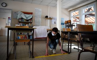 TOPSHOT - French school director Delphine Bediou sets up a classroom to mark social distancing measures at an elementary school, a few days before its reopening, in Clairefontaine-en-Yvelines, on May 7, 2020, on the 52nd day of a strict lockdown in the country aimed at curbing the spread of the COVID-19 (the novel coronavirus). - Primary schools and daycare centres are scheduled to reopen gradually from May 11 in France, then junior high schools the following week -- but only in areas not hit hard by the epidemic, as the country prepares to ease a two-month coronavirus lockdown. (Photo by FRANCK FIFE / AFP) (Photo by FRANCK FIFE/AFP via Getty Images)