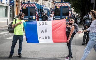 epa09382552 Protesters hold a french flag reading 'No to the Pass' during a demonstration against the COVID-19 health pass which grants vaccinated individuals greater ease of access to venues in France, in Paris, France, 31 July 2021. Anti-vaxxers, joined by the anti-government 'yellow vest' movement, are demonstrating across France for the third consecutive week in objection to the health pass, which is now mandatory for people to  visit leisure and cultural venues.  EPA/CHRISTOPHE PETIT TESSON