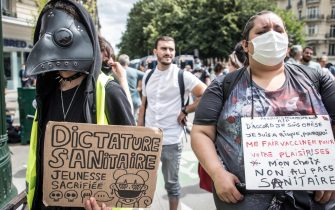 epa09382550 A protester holds a poster reading 'Sanitary Dictature, Youngness sacrified' during a demonstration against the COVID-19 health pass which grants vaccinated individuals greater ease of access to venues in France, in Paris, France, 31 July 2021. Anti-vaxxers, joined by the anti-government 'yellow vest' movement, are demonstrating across France for the third consecutive week in objection to the health pass, which is now mandatory for people to  visit leisure and cultural venues.  EPA/CHRISTOPHE PETIT TESSON