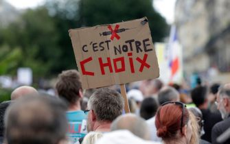 """TOPSHOT - A demonstrator holds a banner reading """"it is our choice"""" during a national day of protest against the compulsory Covid-19 vaccination for certain workers and the compulsory use of the health pass called for by the French government in Paris on July 31, 2021. (Photo by GEOFFROY VAN DER HASSELT / AFP) (Photo by GEOFFROY VAN DER HASSELT/AFP via Getty Images)"""