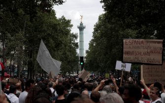Protestors wave banners and placards as they march during a demonstration, part of a national day of protest against French legislation making a Covid-19 health pass compulsory to visit a cafe, board a plane or travel on an inter-city train, in Paris on July 31, 2021. - The legislation passed by parliament the week before has sparked mass protests in France but the government is determined to press ahead and make the health pass a key part of the fight against Covid-19. A valid health pass is generated by two jabs from a recognised vaccine, a negative coronavirus test or a recent recovery from infection. The legislation also makes vaccination compulsory for health-workers and carers. The pass has already been obligatory from July 21 for visits to museums, cinemas and cultural venues with a capacity of more than 50 people. (Photo by GEOFFROY VAN DER HASSELT / AFP) (Photo by GEOFFROY VAN DER HASSELT/AFP via Getty Images)