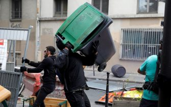 A protester throws a rubbish bin during a demonstration, part of a national day of protest against French legislation making a Covid-19 health pass compulsory to visit a cafe, board a plane or travel on an inter-city train, in Paris on July 31, 2021. - The legislation passed by parliament the week before has sparked mass protests in France but the government is determined to press ahead and make the health pass a key part of the fight against Covid-19. A valid health pass is generated by two jabs from a recognised vaccine, a negative coronavirus test or a recent recovery from infection. The legislation also makes vaccination compulsory for health-workers and carers. The pass has already been obligatory from July 21 for visits to museums, cinemas and cultural venues with a capacity of more than 50 people. (Photo by GEOFFROY VAN DER HASSELT / AFP) (Photo by GEOFFROY VAN DER HASSELT/AFP via Getty Images)