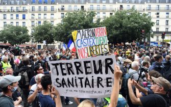 Demonstrators hold up banners and placards, one of which reads as 'Macron, Veran, Castex kill our freedom' and 'Health Terror, I will not submit myself', during a national day of protest against the compulsory Covid-19 vaccination for certain workers and the compulsory use of the health pass called for by the French government in Paris on July 31, 2021. (Photo by Alain JOCARD / AFP) (Photo by ALAIN JOCARD/AFP via Getty Images)