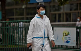 epa09376433 A man wearing a face mask and a protective suit walks at the railway station in Shanghai, China, 29 July 2021. China reported 24 new locally transmitted COVID-19 cases, according to the National Health Commission. More than 170 people have been diagnosed with the Delta variant. The main outbreak is in the eastern city of Nanjing, in Jiangsu province.  EPA/ALEX PLAVEVSKI