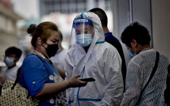 epaselect epa09376431 A traveler shows a health code on a smartphone to a medical personnel at the railway station in Shanghai, China, 29 July 2021. China reported 24 new locally transmitted COVID-19 cases, according to the National Health Commission. More than 170 people have been diagnosed with the Delta variant. The main outbreak is in the eastern city of Nanjing, in Jiangsu province.  EPA/ALEX PLAVEVSKI