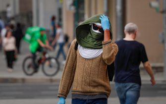 epa09377130 Russian man wearing a protective face mask and gloves walks on the street in Moscow, Russia, 29 July 2021. Russia is facing a third wave of Covid-19 infections amid the ongoing coronavirus pandemic.  EPA/YURI KOCHETKOV