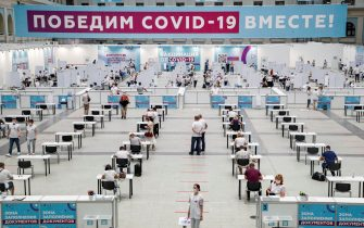 epa09346342 People wait to receive a shot of Russia's Sputnik V vaccine against COVID-19 disease at a vaccination center in Gostinny Dvor, a huge exhibition place in Moscow, Russia, 15 July 2021. More than 500,000 Muscovites received the first component of the coronavirus vaccine in a week. Moscow being the epicentre of the new outbreak of the infections by the new Delta variant. Moscow authorities imposed a ban to serve people without QR-codes confirming vaccination against Covid-19 at public waterings, including people recovering from coronavirus Covid-19 disease within six months before the visit, or negative PCR test taken no earlier than 72 hours before the visit. More than 5,000 cases of COVID-19 were detected in Moscow, 32 per cent more than the day before.  EPA/MAXIM SHIPENKOV