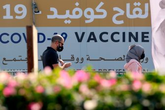 A man and a woman walk past a huge health ministry COVID-19 vaccines announcement outside a medical centre in Dubai on February 16, 2021, as the Gulf emirates goes ahead its vaccination effort. - The UAE, home to a population of around 10 million, has administered some 4.6 million doses of vaccine, making it the second-fastest per capita delivery in the world, after Israel. (Photo by Karim SAHIB / AFP) (Photo by KARIM SAHIB/AFP via Getty Images)