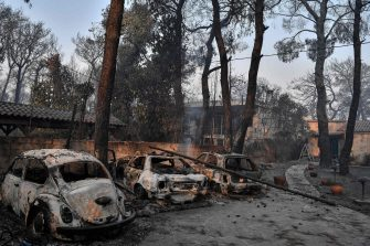 """This photograph taken on August 4, 2021 shows burned cars in Varybombi, a suburb north of Athens, as fires broke out at the foot of Mount Parnes, 30 kilometres north of Athens. - Greek firefighters said in a statement that they hope to bring a forest fire blazing near Athens under control """"in the coming hours"""". More than 500 firefighters, a dozen water-bombing planes and five helicopters have been battling the blazes outside the capital since August 3 afternoon. (Photo by LOUISA GOULIAMAKI / AFP)"""