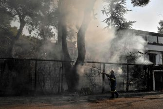 """A fire fighter douses burning trees near residential buildings in Varybombi, a suburb north of Athens, on August 4, 2021, as fires broke out at the foot of Mount Parnes, 30 kilometres north of Athens. - Greek firefighters said in a statement that they hope to bring a forest fire blazing near Athens under control """"in the coming hours"""". More than 500 firefighters, a dozen water-bombing planes and five helicopters have been battling the blazes outside the capital since August 3 afternoon. (Photo by LOUISA GOULIAMAKI / AFP)"""