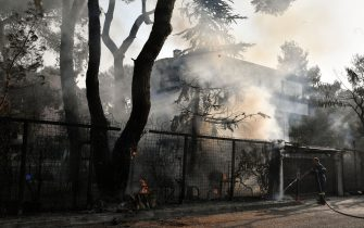 """A fire fighter douse burning trees near residential buildings in Varybombi, a suburb north of Athens, on August 4, 2021, as fires broke out at the foot of Mount Parnes, 30 kilometres north of Athens. - Greek firefighters said in a statement that they hope to bring a forest fire blazing near Athens under control """"in the coming hours"""". More than 500 firefighters, a dozen water-bombing planes and five helicopters have been battling the blazes outside the capital since August 3 afternoon. (Photo by LOUISA GOULIAMAKI / AFP) (Photo by LOUISA GOULIAMAKI/AFP via Getty Images)"""