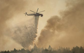 04 August 2021, Greece, Varibobi: A helicopter drops water over a forest fire in the Varibobi area of northern Athens. Photo: Angelos Tzortzinis/DPA (Photo by Angelos Tzortzinis/picture alliance via Getty Images)
