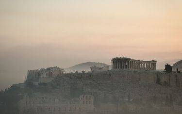 """TOPSHOT - This photograph taken on August 4, 2021 shows smoke covering Athens centre and the Acropolis, due to fires burning at the foot of Mount Parnes, 30 kilometres north of Athens. - Greek firefighters said in a statement that they hope to bring a forest fire blazing near Athens under control """"in the coming hours"""". More than 500 firefighters, a dozen water-bombing planes and five helicopters have been battling the blazes outside the capital since August 3 afternoon. (Photo by LOUISA GOULIAMAKI / AFP) (Photo by LOUISA GOULIAMAKI/AFP via Getty Images)"""