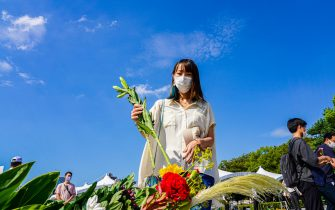A woman wearing a face mask offers flowers at Peace Memorial Park, as Hiroshima marks the 76th anniversary of the atomic bombing.  The atomic bombing which killed about 150,000 people and destroyed the entire city for the first bombing with a nuclear weapon in a war. (Photo by Jinhee Lee / SOPA Images/Sipa USA)