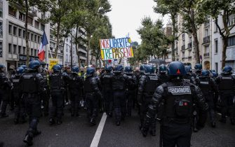 epa09404304 Protesters surrounded by anti-riot forces march during a demonstration against the COVID-19 health pass which grants vaccinated individuals greater ease of access to venues in France, in Paris, France, 07 August 2021. The national enforcement of the 'Health Pass' is expected to take effect on 09 August, after the French Constitutional Council has confirmed the government's law which extend the use of its Vaccinal Passeport (a QR code which proves the bearer has received full vaccination, or been tested negative for Covid in the last 72 hours) to cultural place, transport, and restaurants among other places.  EPA/IAN LANGSDON