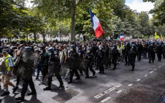 epa09404308 Protesters surrounded by anti-riot forces march during a demonstration against the COVID-19 health pass which grants vaccinated individuals greater ease of access to venues in France, in Paris, France, 07 August 2021. The national enforcement of the 'Health Pass' is expected to take effect on 09 August, after the French Constitutional Council has confirmed the government's law which extend the use of its Vaccinal Passeport (a QR code which proves the bearer has received full vaccination, or been tested negative for Covid in the last 72 hours) to cultural place, transport, and restaurants among other places.  EPA/IAN LANGSDON