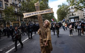 epa09404309 A protester dressed as Jesus holds a cross bearing the message 'the vaccine kills your immune system', during a demonstration against the COVID-19 health pass which grants vaccinated individuals greater ease of access to venues in France, in Paris, France, 07 August 2021. The national enforcement of the 'Health Pass' is expected to take effect on 09 August, after the French Constitutional Council has confirmed the government's law which extend the use of its Vaccinal Passeport (a QR code which proves the bearer has received full vaccination, or been tested negative for Covid in the last 72 hours) to cultural place, transport, and restaurants among other places.  EPA/IAN LANGSDON
