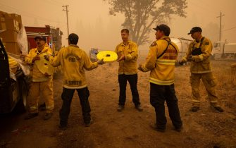epa09404929 Firefighters unload hose lines as they fight the Dixie Fire in Greenville, California, USA, 07 August 2021. The Dixie Fire had grown to over 440,000 acres as of 07 August.  EPA/CHRISTIAN MONTERROSA