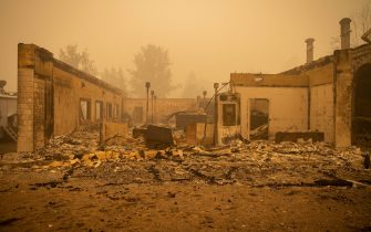 epa09404932 Buildings and vehicles are left destroyed by the Dixie Fire in Greenville, California, USA, 07 August 2021. The Dixie Fire had grown to over 440,000 acres as of 07 August.  EPA/CHRISTIAN MONTERROSA