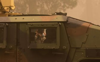 epa09404938 A member of the National Guard puts on an N95 mask at the Dixie Fire near Greenville, California, USA, 07 August 2021. The Dixie Fire had grown to over 440,000 acres as of 07 August.  EPA/CHRISTIAN MONTERROSA