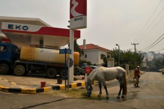 A man walks past a horse eating hay near a gas station as a fire spreads in the village of Afidnes, some 30 kilometres north of Athens on August 6, 2021. - Hundreds of firefighters battled a blaze on the outskirts of Athens on August 6 as dozens of fires raged in Greece. (Photo by LOUISA GOULIAMAKI / AFP) (Photo by LOUISA GOULIAMAKI/AFP via Getty Images)