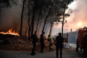 A fireman rushes to extinguish a fire spreading near houses in Thrakomakedones, near Mount Parnitha, north of Athens, on August 7, 2021. - Hundreds of firefighters battled a blaze on the outskirts of Athens as several fires raged in Greece. (Photo by Louisa GOULIAMAKI / AFP) (Photo by LOUISA GOULIAMAKI/AFP via Getty Images)