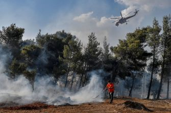 A local resident fights fire restart in Thrakomakedones, near Mount Parnitha, north of Athens, on August 7, 2021. - Hundreds of firefighters battled a blaze on the outskirts of Athens as several fires raged in Greece. (Photo by Louisa GOULIAMAKI / AFP) (Photo by LOUISA GOULIAMAKI/AFP via Getty Images)