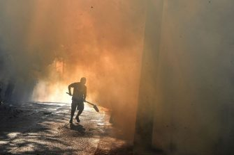 A local resident runs to fight a fire in Thrakomakedones, near Mount Parnitha, north of Athens, on August 7, 2021. - Hundreds of firefighters battled a blaze on the outskirts of Athens as several fires raged in Greece. (Photo by Louisa GOULIAMAKI / AFP) (Photo by LOUISA GOULIAMAKI/AFP via Getty Images)