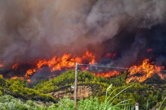 A forest fire engulfs the forest of a mountain side in the area of Platanos village, near ancient Olympia in western Greece on August 4, 2021. - Greek firefighters have been battling several heatwave-fuelled forest infernos, including around Athens that have destroyed or damaged dozens of homes and businesses and forced the evacuation of villages, and others in the south and on the island of Euboea. (Photo by STR / Eurokinissi / AFP) (Photo by STR/Eurokinissi/AFP via Getty Images)