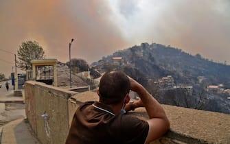 Un uomo guarda in lontananza uno degli incendi scoppiati in Algeria