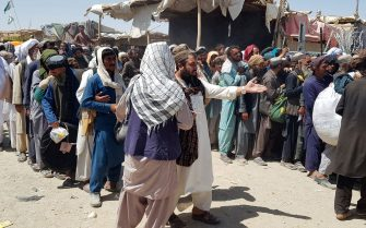 Stranded Afghan nationals stand in queues as they wait for the reopening of the Pakistan-Afghanistan border crossing point in Chaman on August 13, 2021, after the Taliban took control of the Afghan border town in a rapid offensive across the country. (Photo by - / AFP) (Photo by -/AFP via Getty Images)