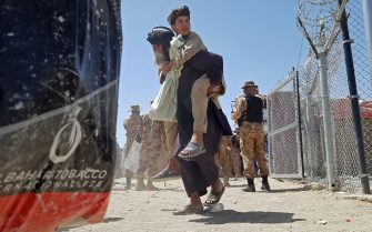 A stranded Afghan national carries his son at the Pakistan-Afghanistan border crossing point in Chaman on August 13, 2021, after the Taliban took control of the Afghan border town in a rapid offensive across the country. (Photo by - / AFP) (Photo by -/AFP via Getty Images)